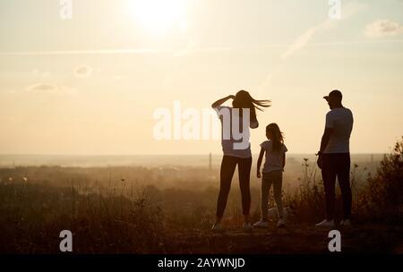 Silhouette einer Familie, die mit dem Rücken zur Kamera auf dem Hügel steht und beim Sonnenuntergang zum Horizont blickt und sich vom langen und aktiven Tag verabschiedet - Stockfoto