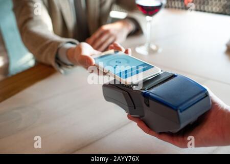 Horizontaler Nahaufnahme mit hohem Winkel von nicht erkennbarem Mann, der mit NFC auf dem Smartphone für das Essen im Restaurant bezahlt - Stockfoto