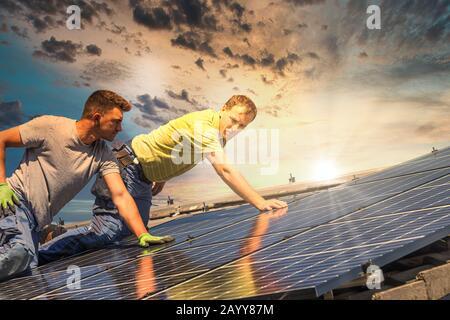 Porträt der Arbeiter, die Fotovoltaikanlagen auf dem Dach installieren - Stockfoto