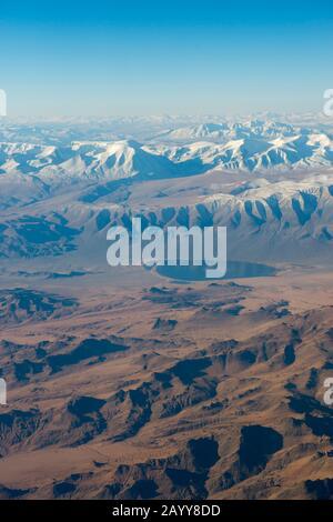 Blick auf das schneebedeckte Altai-Gebirge (Altay-Gebirge) in der Nähe von Ulgii auf dem Flug von Ulaanbaatar nach Ulgii (Ölgii) in der westlichen Mongolei. - Stockfoto