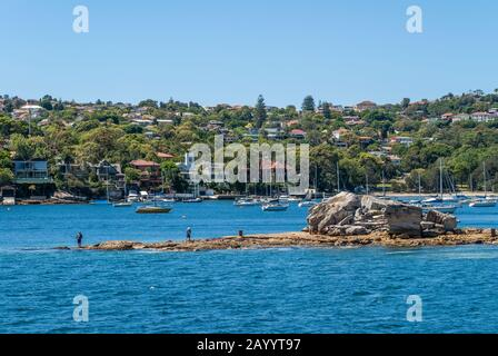 Sydney, Australien - 11. Dezember 2009: Ein Paar Fischer versuchen ihr Glück auf einer sndy Felsenislet, die aus blauem Erkerwasser mit grünem Ufer voller ist - Stockfoto