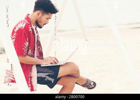 Ein gutaussehender Mann, der einen Laptop verwendet, der von überall aus arbeitet. - Stockfoto