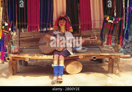 Thailand: Padaung (Long Neck Karen) spielt eine hausgemachte Gitarre, Dorf in der Nähe von Mae Hong Son. Die Padaung oder Kayan Lahwi oder langhalsige Karen sind eine Untergruppe der Kayan, eine Mischung aus law-Stamm, Kayan Stamm und mehrere andere Stämme. Kayan sind eine Untergruppe der Roten Karen (Karenni), eine tibeto-burmanische ethnische Minderheit von Burma (Myanmar). Stockfoto
