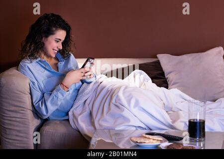 Eine junge Frau, die auf dem Sofa sitzt und auf ihr Telefon schaut und lächelt - Stockfoto