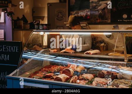 London, Großbritannien - 29. November 2019: Frau schneidet Fleisch auf einem Fleisch- und Geflügelstand im Borough Market, einem der größten und ältesten Lebensmittelmärkte Londons - Stockfoto