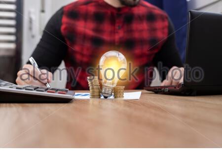 Ein Schreibtisch mit einer Glühbirne und Geld, auf den ein Mann sich auf seine Arbeit konzentrierte - Stockfoto