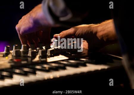Ein Nahselektiver Fokus, der auf die Hände eines Mannes geschossen wurde, der eine elektronische Tastatur spielt, und während einer Nacht, die auf einem multikulturellen Festival veranstaltet wurde, die Wahltasten dreht - Stockfoto