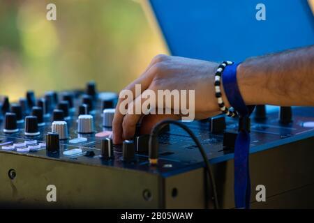 Nahansicht eines elektronischen Musik-DJ, der Wählscheiben auf einem CDJ-Mixer dreht, mit Bangen vor grünem, verschwommenen Hintergrund beim Earth Festival - Stockfoto
