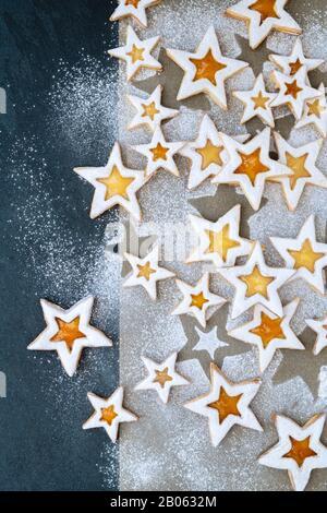 Hausgemachte Lemon- und Peach Linzer Cookies. Zitronenschrot und Pfirsich erhalten Stern-Sandwichkekse mit Puderzucker auf Pergament und Schieferhintergrund - Stockfoto