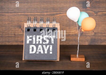 Erster Tag. Geburtstag, Arbeit, Schule und Urlaubskonzept. Notizbuch und bunte Ballons auf dem Holzhintergrund Stockfoto