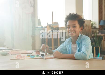 Porträt des afrikanischen jungen Jungen, der beim Sitzen am Tisch mit der Kamera lächelt und ein Bild mit Farben und Pinsel zeichnet Stockfoto