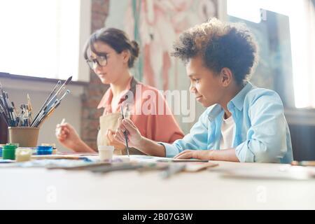 Junge Frau, die zusammen mit dem afrikanischen Jungen am Tisch sitzt und im Kunststudio mit Aquarellen malt Stockfoto