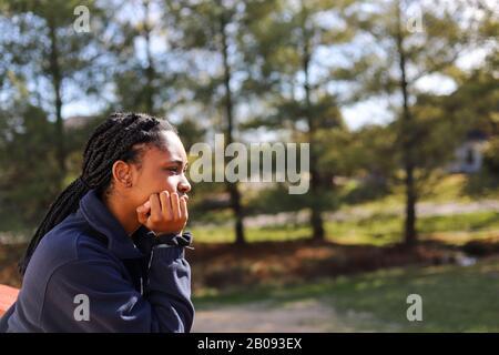 Porträt eines afroamerikanischen Teenagermädchens, das tief überlegt wegschaut - Stockfoto