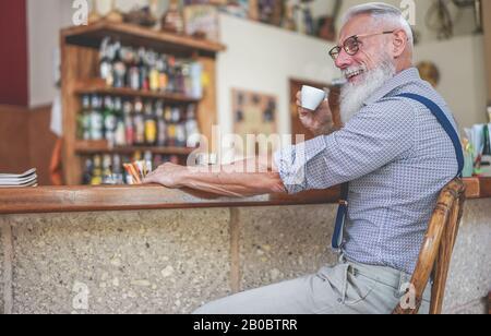 Fröhlicher Senior trinkt Kaffee in der Vintage-Bar - Fashion Old Guy hat Spaß beim Frühstück - Fröhliches älteres Lifestyle-Konzept - Konzentriert sich auf seinen FAC - Stockfoto