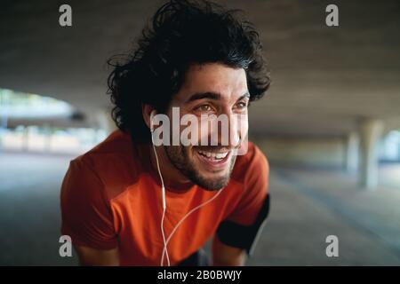 Nahporträt eines erschöpften, jungen glücklichen Mannes mit Ohrhörer in den Ohren, der nach dem Joggen im Park Pause macht - Neujahrsbeschlüsse