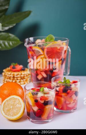 Rotwein frischer Sangria oder Stanzen mit Früchten, Minzblättern und Beeren. Hausgemachte Waffeln im Hintergrund - Stockfoto