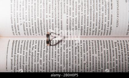 Ehering zwischen den Seiten eines Buches mit dem Sonnenlicht wirft einen herzförmigen Schatten