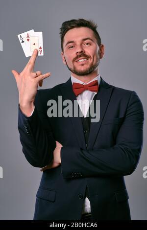 Mann in schwarzem klassischem Anzug und roter Krawatte, die zwei Spielkarten zeigen, während sie vor grauem Studiohintergrund posieren. Glücksspiel, Poker, Casino. Nahaufnahme. - Stockfoto