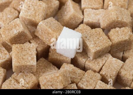 Nahaufnahme des Makrostudios mit einem weißen Zuckerklumpen auf braunen Zuckerwürfeln - Stockfoto