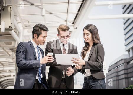 Geschäftsleute sprechen über Arbeit, während sie sich außerhalb treffen, arbeiten Geschäftspartner zusammen. - Stockfoto