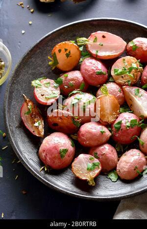 Nahaufnahme von geröstetem Rettich auf Platte über dunklem Teller. Vegetarisches veganes Essenskonzept.