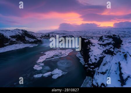 Sonnenuntergang über dem Godafoss Wasserfall mit Eis und Schnee im Winter, Hochland, Island