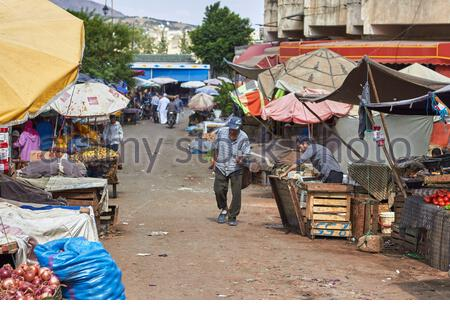 Ein Mann, der mitten auf einem Obst- und Gemüsemarkt in Fes die Straße hinunter läuft. - Stockfoto