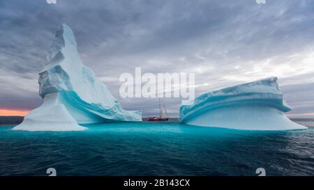 Eisberge und Segelboot in der Diskobucht auf Mittsommer, Grönland