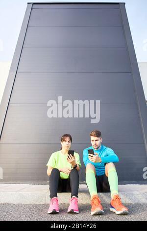 Läufer, die ihre Aktivität am Telefon nach einem Rennen überprüfen - Sportkonzept, Training - Stockfoto