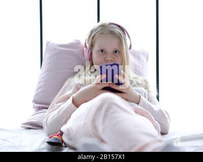 Modernes Leben der Generation z. Teenager-Mädchen in Schlafanzug und Kopfhörer im Zimmer auf dem Bett hört Musik von einem Smartphone. - Stockfoto