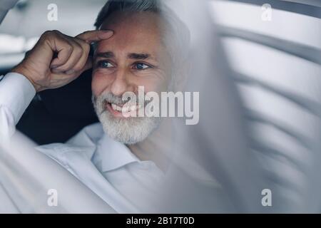 Porträt eines lächelnden, reifen Geschäftsmannes in seinem Auto, der auf Distanz blickt - Stockfoto