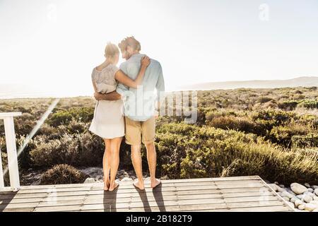 Liebevolles junges Paar umarmt auf Terrasse an der Küste im Sommer - Stockfoto