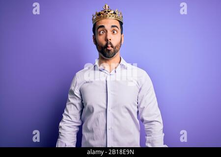 Junger gutaussehender Mann mit Bart mit goldener Königskrone über violettem Hintergrund, der Fischgesicht mit Lippen, verrückter und komischer Geste macht. Lustiger Express - Stockfoto