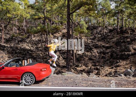 Junge, stilvolle Frau mit dem Auto unterwegs, Jumpimg aus dem Kofferraum am Straßenrand im Wald. Sorgloses Lifestyle- und Reisekonzept - Stockfoto
