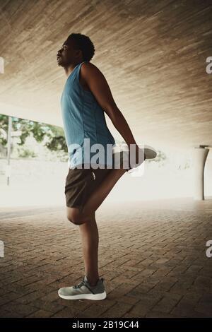 Fitness-Männchen in Sportbekleidung, die im Freien trainieren und dabei ein Bein Strecken, während sie unter der Brücke stehen Stockfoto