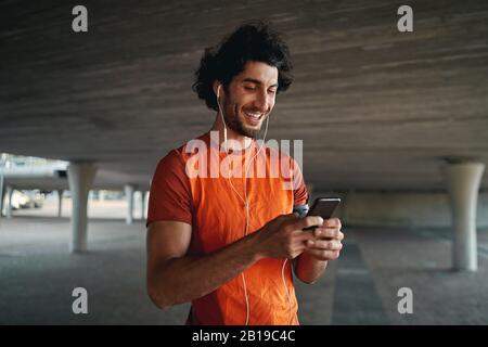 Porträt eines lächelnden jungen männlichen Läufers, der unter der Betonbrücke steht, mit Ohrhörer in den Ohren, der auf einem Smartphone tippt Stockfoto