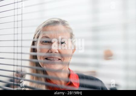 Durch die Jalousien: Erfolgreiche Geschäftsfrau, die durch das Bürofenster schaut - Stockfoto