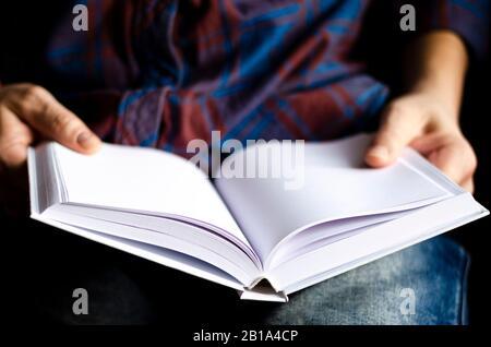 Weißes Buch mit sauberen Seiten in den Händen eines Mannes - Stockfoto