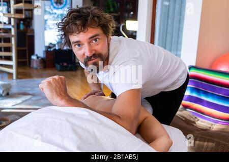 Frau, die Rückenmassage erhält. Mittelaufnahme des Therapeuten, der in gemütlicher häuslicher Umgebung eine Massage auf Frau abmassiert. Körperpflege - Stockfoto