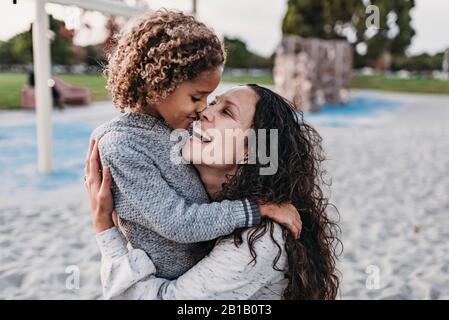Nahaufnahme von glücklichen Mutter und Sohn umarmen eng auf dem Spielplatz