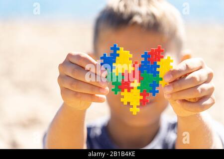 Junge, der buntes Puzzleherz vor seinem Gesicht hält. Weltautismus Bewusstsein Tag Konzept - Stockfoto