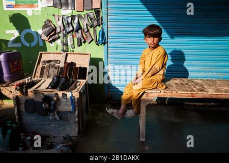 Junge, der im Cobblers Shop sitzt - Stockfoto