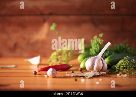 Gurken in Dosen beizen. Zutaten für marinierte Gherkins, Glasbecher, Knoblauch, Dill, Salz, Pfeffer auf grünem Hintergrund. Kopierbereich. Konzept der Gemüsekonservierung - Stockfoto