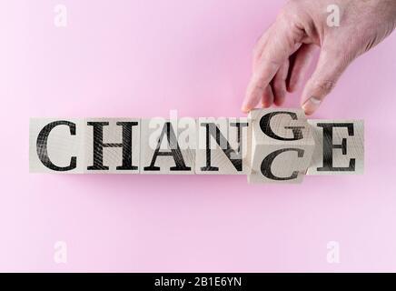 Hand dreht Wort IN CHANCE auf Holzklötze vor pinkfarbenem Hintergrund - Stockfoto