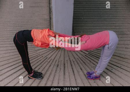Junge, gesunde weibliche Läufer während einer Trainingsroutine in der Stadt - Stockfoto