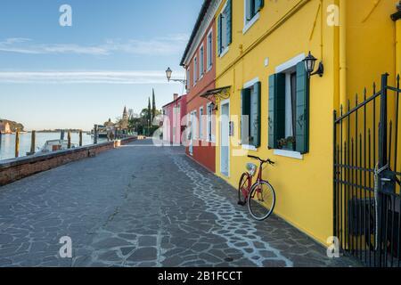 Fahrrad vor einem gelben Haus in Burano (Venedig, Italien) an einem sonnigen Tag im Winter - Stockfoto