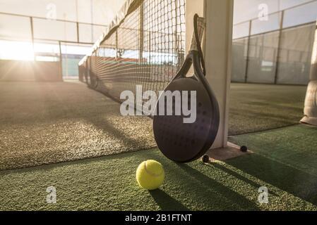 Paddeln Sie Tennisschläger und -Ball im Bild bei Sonnenuntergang auf dem Außenplatz - Stockfoto