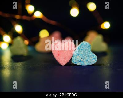 Zwei herzförmige Süßigkeiten. Rosa und blaue Herzen im Fokus und wenige Süßigkeiten in verschiedenen Farben auf verschwommem Hintergrund. Konzept des Valentinstages oder Ernährung su