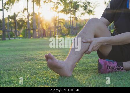Der junge Mann massiert seine schmerzhaften Wadenschmerzen beim Joggen und draußen im Park. Sport- und Trainingskonzept. - Stockfoto