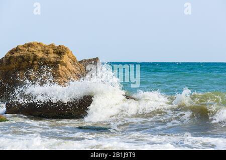 Wellen brechen auf großen Steinen und Felsen und machen viel Spritzer. Schöner Meerblick. - Stockfoto